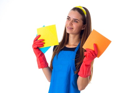 Positive young woman in blue T-shirt and apron with red gloves holding dusters on white background in studio