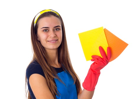 Pleasant young woman in blue T-shirt and apron with red gloves holding dusters on white background in studio