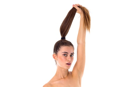 ponytail: Young attractive woman holding long ponytail on white background in studio Stock Photo