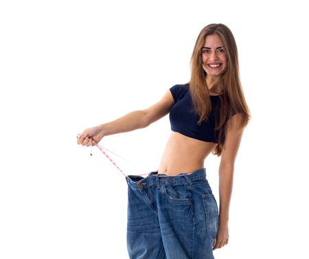 Smiling young woman with long brown hair holding her  jeans of much bigger size with centimeter on white background in studio