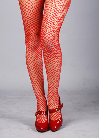 fetishes: beautiful female legs in red mesh stockings Stock Photo