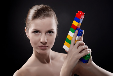 plaything: portrait of young beautiful woman with toy gun