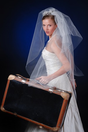 young bride with heavy travelling bag on a black background