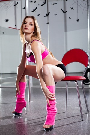 stripper pole: young beautiful woman in pink sportswear on the red chair  Stock Photo
