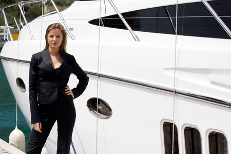 white suit: beautiful woman in black suit near the white yacht Stock Photo