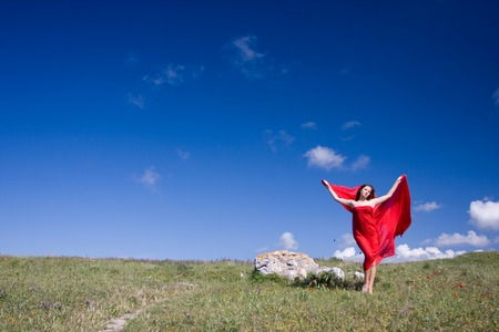 standing stone: young beautiful woman in red dress standing on the field