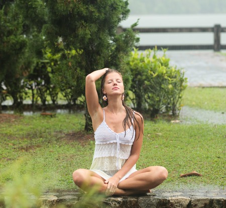 parapet: Beautiful young woman with closed eyes sitting on the parapet in the rain