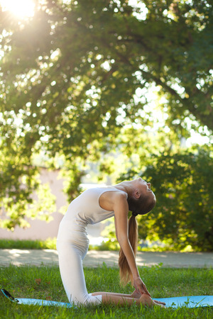 arching: Beautiful young woman practices yoga in nature; standing on her knees, arching back and keeping her feet hands