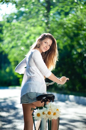 clinging: Beautiful young woman in a blouse and shorts clinging to an old bicycle handlebars. Back view