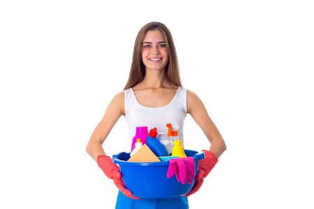 Young pretty woman in white shirt and blue apron with red gloves holding cleaning things in blue washbowl on white background in studio Stock Photo