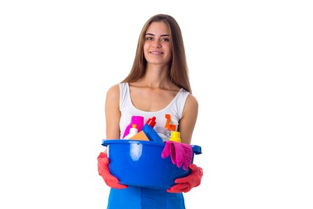 Young attractive woman in white shirt and blue apron with red gloves holding cleaning things in blue washbowl on white background in studio