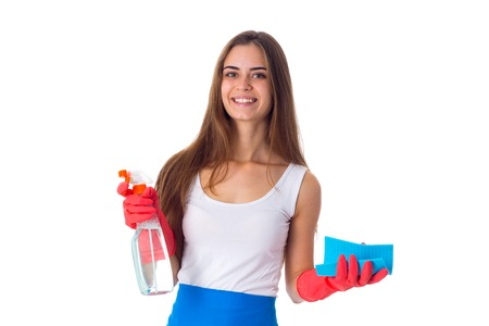 Young smiling woman in white shirt and blue apron with red gloves holding duster and detergent on white background in studio