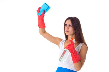 Young serious woman in white shirt and blue apron with red gloves using duster and detergent on white background in studio Stock Photo
