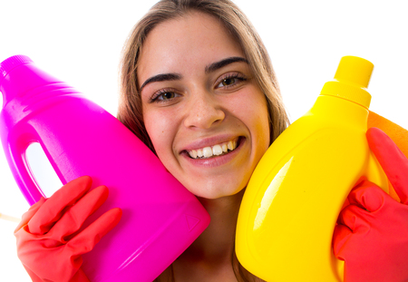 Charming young woman in white shirt and red gloves holding duster and detergents on white background in studio