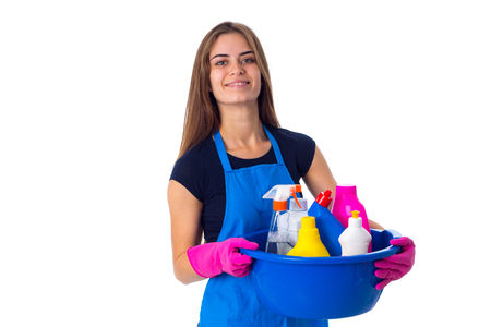 washbowl: Young positive woman in blue T-shirt and apron with pink gloves holding cleaning things in blue washbowl on white background in studio Stock Photo