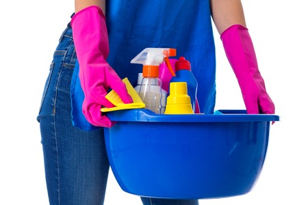 washbowl: Young woman in blue jeans and apron with pink gloves holding cleaning things in blue washbowl on white background in studio Stock Photo