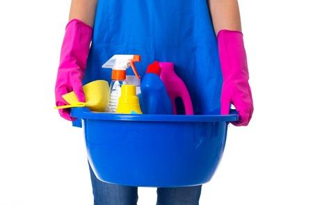 Młoda kobieta w niebieskim fartuchu i dżinsy z różowym rękawice gospodarstwa rzeczy czyszczenia w niebieskim umywalka na białym tle w studio