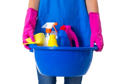 Young woman in blue apron and jeans with pink gloves holding cleaning things in blue washbowl on white background in studio