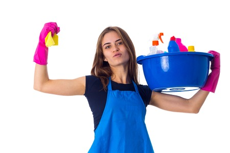 washbowl: Young pretty woman in blue T-shirt and apron with pink gloves holding cleaning things in blue washbowl and showing muscules on white background in studio.