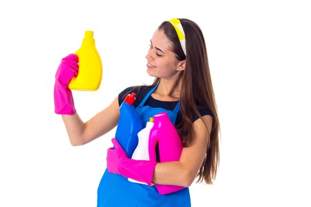 charwoman: Positive young woman in blue T-shirt and apron with pink gloves holding detergents on white background in studio Stock Photo