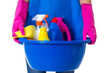 washbowl: Young woman in blue apron with pink gloves holding cleaning things in blue washbowl on white background in studio Stock Photo