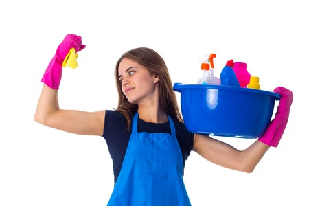 Young attractive woman in blue T-shirt and apron with pink gloves holding cleaning things in blue washbowl and showing muscules on white background in studio.
