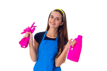 Positive young woman in blue T-shirt and apron holding pink gloves and detergent on white background in studio