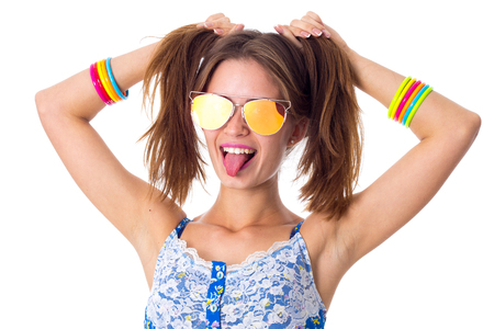ponytails: Young smiling woman in blue T-shirt with varicoloured bracelets and sunglasses making ponytails and showing her tongue on white background in studio