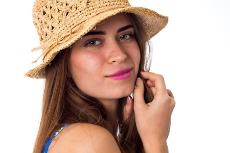 Young beautiful woman with long brown hair in blue shirt with cute hat smiling on white backgroung in studio