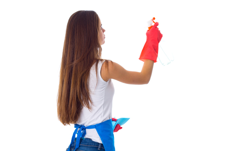 Young woman in white shirt, jeans and blue apron with gloves using blue duster and detergent on white background in studio