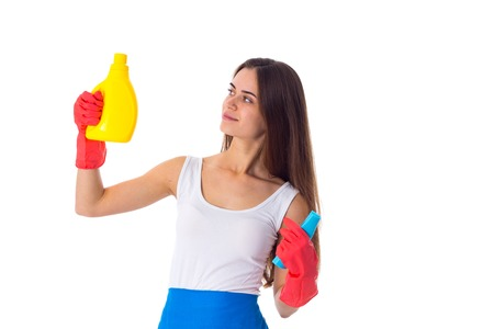 Pretty young woman in white shirt and blue apron with red gloves holding duster and detergent on white background in studio