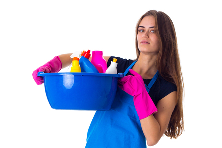 washbowl: Young serious woman in blue T-shirt and apron with pink gloves holding cleaning things in blue washbowl on white background in studio Stock Photo