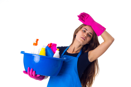 Young tired woman in blue T-shirt and apron with pink gloves holding cleaning things in blue washbowl on white background in studio Stock Photo