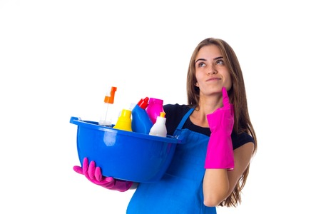Young wondering woman in blue T-shirt and apron with pink gloves holding cleaning things in blue washbowl on white background in studio