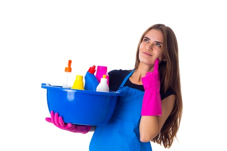Young charming woman in blue T-shirt and apron with pink gloves holding cleaning things in blue washbowl on white background in studio