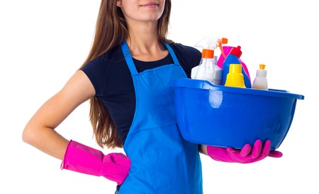 washbowl: Young woman in blue T-shirt and apron with pink gloves holding cleaning things in washbowl on white background in studio Stock Photo