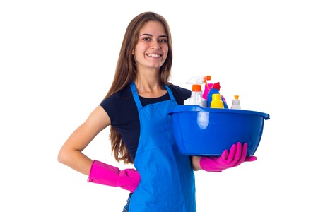 Young nice woman in blue T-shirt and apron with pink gloves holding cleaning things in blue washbowl on white background in studio