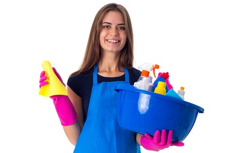 washbowl: Young pleasant woman in blue T-shirt and apron with pink gloves holding cleaning things in blue washbowl on white background in studio Stock Photo