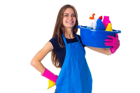 Smiling young woman in blue T-shirt and apron with pink gloves holding cleaning things in blue washbowl on white background in studio