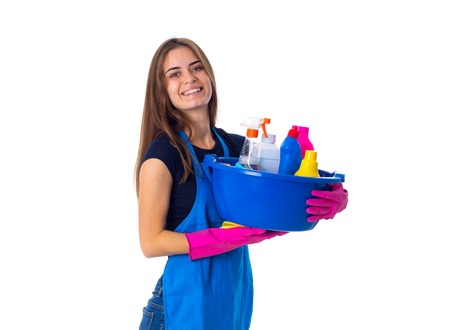 Pretty young woman in blue T-shirt and apron with pink gloves holding cleaning things in blue washbowl on white background in studio