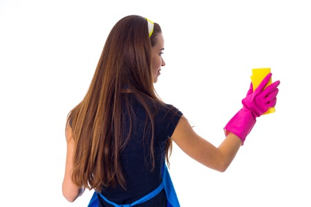 Young woman in blue T-shirt and apron with pink gloves using a duster on white background in studio