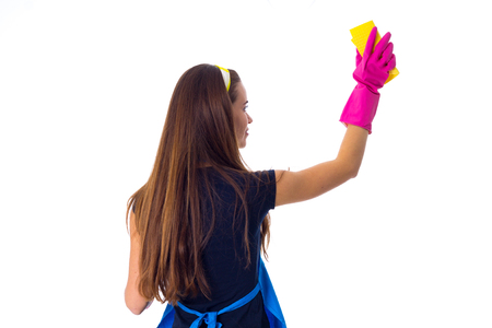 Young woman with long hair in blue T-shirt and apron with pink gloves using yellow duster on white background in studio