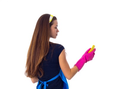 Young woman with long brown hair in blue T-shirt and apron with pink gloves using yellow duster and detergent on white background in studio Stock Photo
