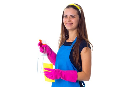 Young happy woman in blue T-shirt and apron with pink gloves holding yellow duster and detergent on white background in studio