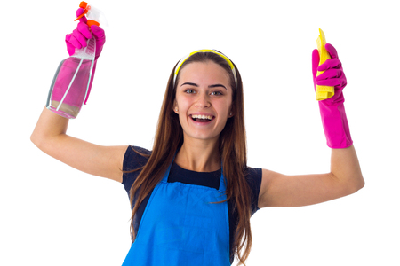 Smiling young woman in blue T-shirt and apron with pink gloves holding yellow duster and detergent on white background in studio