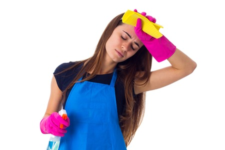 charwoman: Tired young woman in blue T-shirt and apron with pink gloves holding duster and detergent on white background in studio