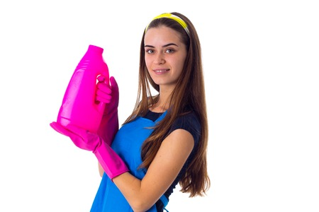 Young attractive woman in blue T-shirt and apron with pink gloves holding detergent on white background in studio Stock Photo