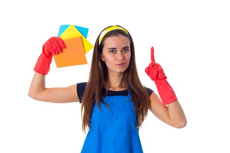 Young beautiful  woman in blue T-shirt and apron with red gloves holding dusters and showinh finger up on white background in studio