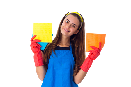 Young good-looking woman in blue T-shirt and apron with red gloves holding dusters on white background in studio