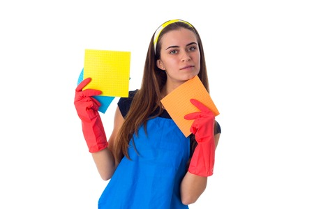Beautiful young woman in blue T-shirt and apron with red gloves holding dusters on white background in studio